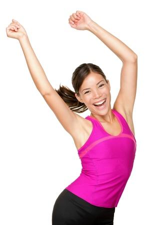 Gelukkig fitness dansen. Vrouw danser vrolijk, blij en lachend met opgeheven armen. Asian  Caucasian fitness model geïsoleerd op een witte achtergrond. Stockfoto