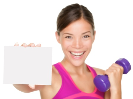 fitness sign woman smiling happy showing empty blank paper sign. Fitness model isolated on white background. Stock Photo