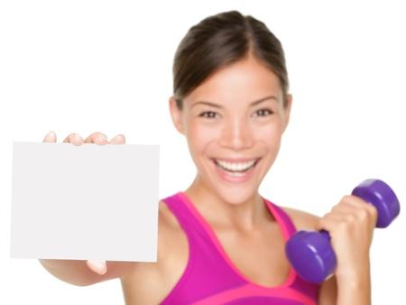 fitness teken vrouw lachend blij dat hij leeg is blanco papier ondertekenen. Fitness model geïsoleerd op een witte achtergrond.