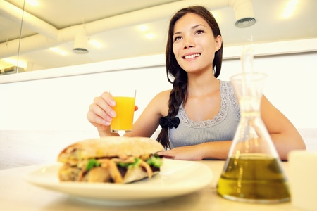 Cafe woman eating sandwich and drinking juice. Cute young asian woman. photo