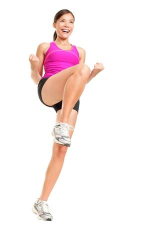 Fitness vrouw aerobicsinstructeur uitoefening van geïsoleerde in volledige lichaam. Gelukkig lachend en energieke fit vrouwelijke fitness model in roze top.