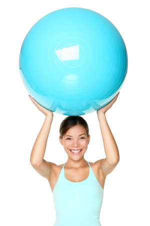 Pilates fitness woman isolated exercising with exercise ball during workout. Beautiful smiling happy mixed race Chinese Asian  Caucasian fit female fitness woman isolated on white background.