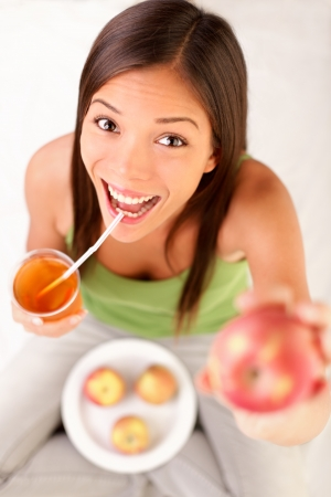 apple juice woman drinking apple juice showing apples. Happy excited and cheerful young female model. photo