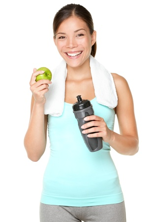 Healthy lifestyle - fitness woman eating apple smiling happy looking at camera. Pretty mixed race Caucasian Asian woman isolated on white background. photo