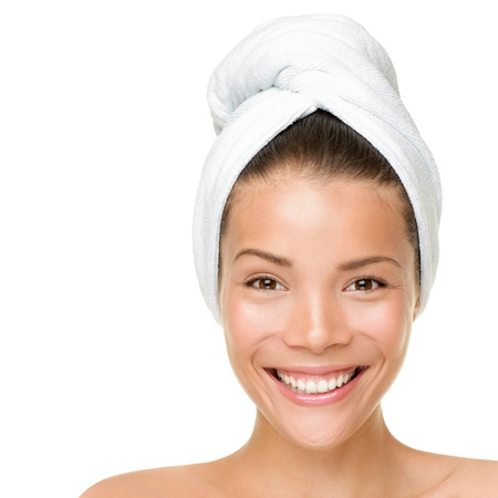 Beauty spa treatment woman wearing towel drying hair. Closeup portrait of happy smiling beautiful Caucasian / Asian female model isolated on white background.