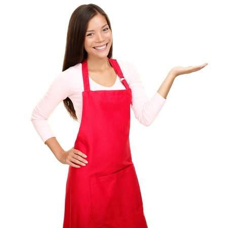 vendedor: Propietario de la peque�a tienda mostrando espacio vac�o copia en delantal rojo. Mujer sonriendo feliz presentando con la Palma de la mano abierta. Amistoso multirracial asi�ticos cauc�sica modelo femenino aislada sobre fondo blanco