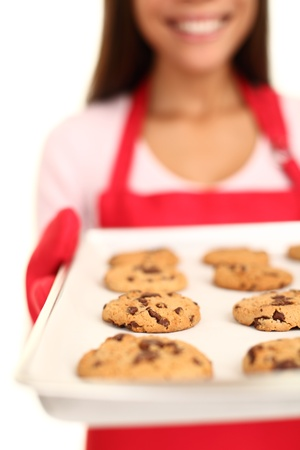 bakery shop: Baking chocolate chip cookies. Woman showing tray with fresh baked cookies over white. Shallow depth of field. Stock Photo