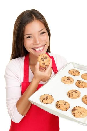 cookie chocolat: femme de cuisson manger biscuits frais sortis du four. Bonne sourire m�tis chinois asiatiques  blanc de cuisine caucasienne � la maison. Isol� sur fond blanc.
