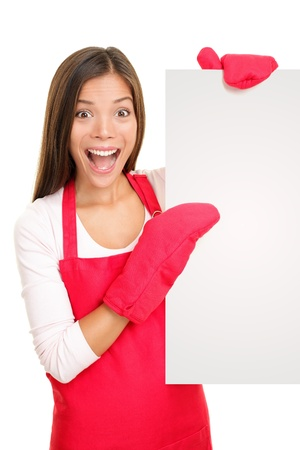 food sales: Baking woman showing blank poster sign wearing cooking mittens and red apron. Excited happy smiling mixed race Chinese Asian  white Caucasian woman isolated on white background.