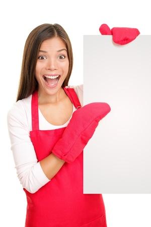 Bakken vrouw met lege poster teken dragen van koken wanten en rode schort. Opgewonden gelukkig lachend gemengd ras Chinees Aziatisch  wit blanke vrouw op een witte achtergrond.