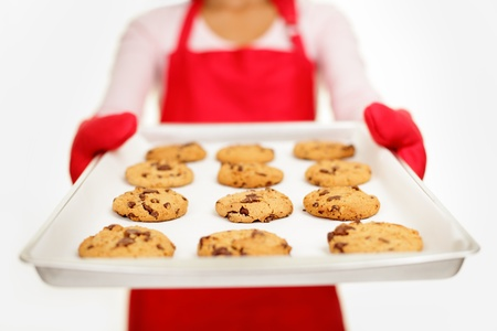 baking cookies: chocolate chip cookies - baking woman. Housewife showing tray with fresh baked cookies on white background. Shallow depth of field.