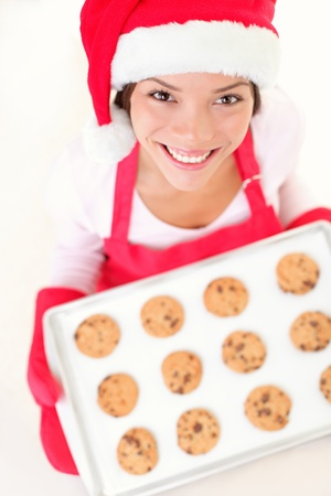 baking tray: Christmas baking santa woman smiling happy having fun with Christmas preparations wearing Santa hat. Mixed race Chinese Asian and Caucasian female model making christmas cookies.