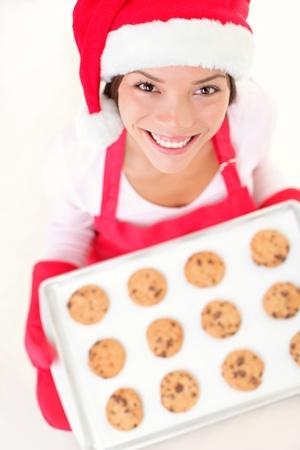 baking cookies: Cottura Babbo Natale donna sorridente felice divertente avere con i preparativi di Natale indossando cappello di Babbo. Razza mista cinese modello asiatico e caucasica femminile facendo biscotti di Natale. Archivio Fotografico