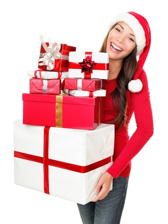 christmas shopping: Asian christmas santa woman shopping holding many gifts wearing santa hat smiling happy. Beautiful female model isolated on white background. Stock Photo