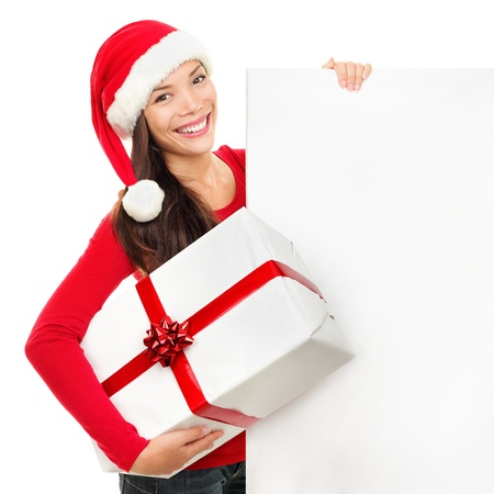 Beautiful christmas woman in santa hat holding empty board sign isolated on white background. Stock Photo