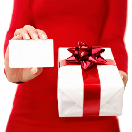 Christmas present and gift card. Woman holding gift card or business card while showing christmas present. Red and white colors. Closeup isolated on white background.
