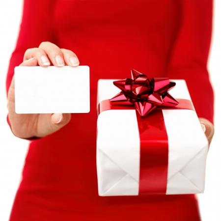 gifts: Kerstcadeau en cadeau-kaart. Vrouw met gift card of visitekaartje terwijl het tonen van kerstcadeau. Rode en witte kleuren. Close-up geïsoleerd op een witte achtergrond.