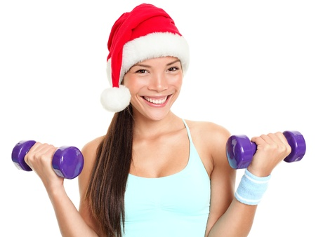 Christmas fitness sport woman wearing santa hat doing gym excersise training arms lifting dumbbells. Mixed race Chinese Asian Caucasian female fitness model isolated on white background. Stock Photo