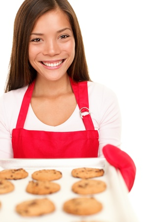 baking woman showing cookies on oven tray. Happy smiling mixed race Chinese Asian  white Caucasian cooking at home. Isolated on white background. photo
