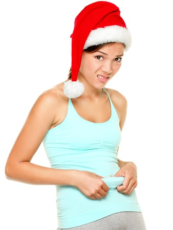 Christmas fitness woman - funny weight loss concept of fit young woman showing her belly fat after Christmas. Young female asian caucasian model isolated on white background. photo