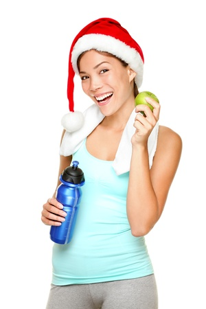 Christmas fitness sport woman wearing santa hat eating apple. Mixed race Chinese Asian Caucasian female fitness model isolated on white background. Stock Photo - 10697012