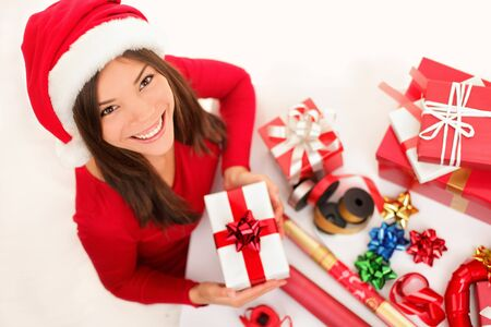 Christmas santa womant preparing gifts wrapping paper for holidays. Beautiful asian caucasian girl smiling.