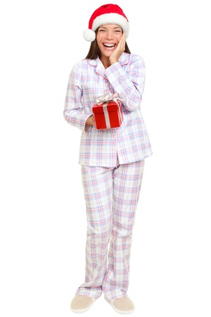 pyjamas: christmas morning santa woman holding gift wearing pajamas smiling happy and excited isolated on white in full body. Multiracial Asian Caucasian santa girl standing