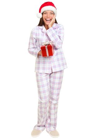 pijama: la mañana de Navidad de Santa mujer con pijamas regalo lleva sonriendo feliz y emocionado aislado en blanco en el cuerpo. Multirracial Asiático Caucásico Santa chica de pie Foto de archivo
