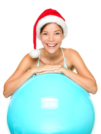 fitness model: Christmas fitness woman on exercise ball wearing santa hat smiling joyful and happy. Beautiful cheerful mixed race Asian Caucasian female fitness model isolated on white background. Stock Photo