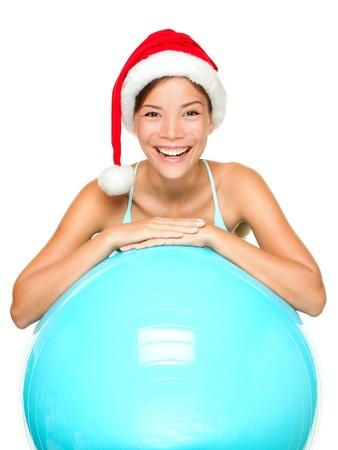 Kerst fitness vrouw op oefening bal het dragen van santa hoed lachend blij en gelukkig. Mooie vrolijke gemengd ras Aziatische blanke vrouw fitness model op een witte achtergrond. Stockfoto