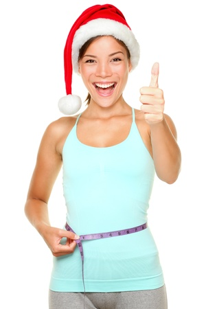 Christmas weight loss concept. Fitness woman wearing santa hat measuring waist with measuring tape while showing thumbs up success sign and smiling happy and cheerful. Beautiful young multi-cultural female model isolated on white background. Archivio Fotografico