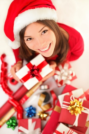Christmas gifts. Woman wrapping christmas presents wearing santa hat. Christmas preparations concept with beautiful smiling happy content young woman in her twenties. Archivio Fotografico