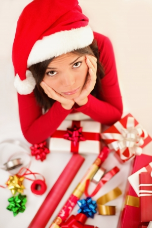 Sad christmas santa woman wrapping gifts depressed and bored wearing santa hat. Caucasian asian female model. photo