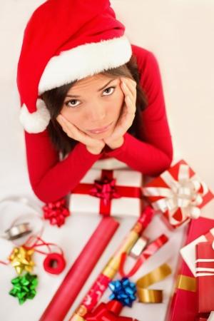 Sad christmas santa woman wrapping gifts depressed and bored wearing santa hat. Caucasian asian female model.