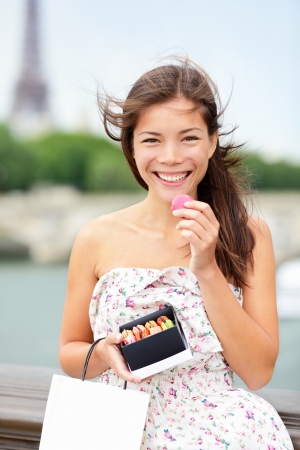 Paris woman eating macaroon with Seine and Eiffel Tower in background. Beautiful woman tourist holding macaroon box and shopping bag. Archivio Fotografico
