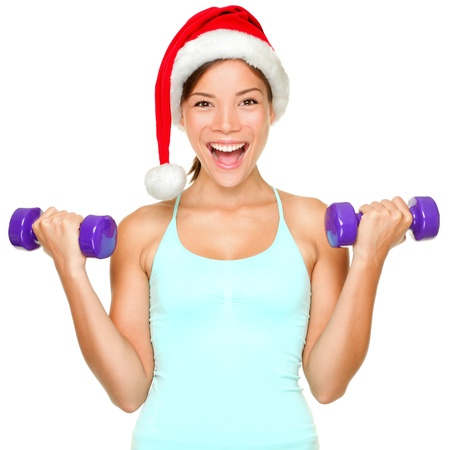 fitness model: Fitness christmas woman training lifting hand weight wearing santa hat. Female model working out smiling happy and excited isolated on white background. Stock Photo