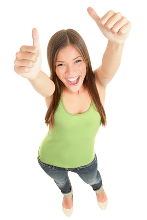 Happy woman giving thumbs up success hand sign standing excited and cheerful isolated in full length on white background. Young fresh and beautiful mixed race Caucasian Asian female model in her 20s. Stock Photo