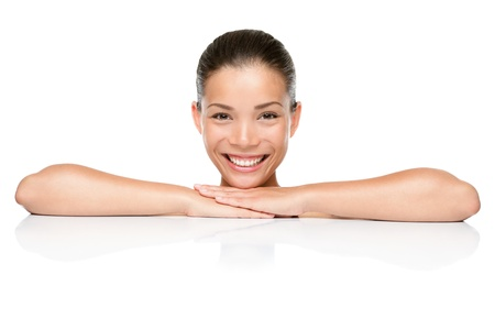 asian model: Beauty. Spa skin care woman smiling happy leaning face and arms on white blank copy space or edge. Beautiful mixed race Asian Caucasian female model isolated on white background. Stock Photo