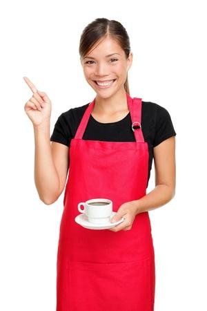 delantal: Camarera o barista apuntando caf� de explotaci�n. Mujer en delantal sonriendo feliz aislada sobre fondo blanco.