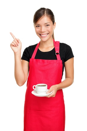 Waitress or barista pointing holding coffee. Woman in apron smiling happy isolated on white background. photo