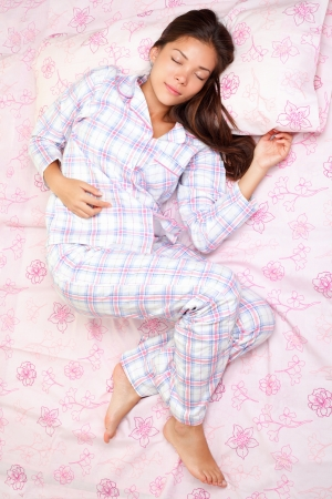 bed sheet: Sleeping woman in bed having beauty sleep in pajamas. Beautiful cute girl in her twenties. Asian Caucasian female model in full length lying down. High angle view. Stock Photo
