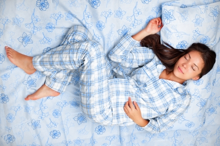 one sheet: Sleep. Woman sleeping in bed having beauty sleep in pajamas. Beautiful cute girl in her twenties. Asian Caucasian female model in full body lying down. Stock Photo