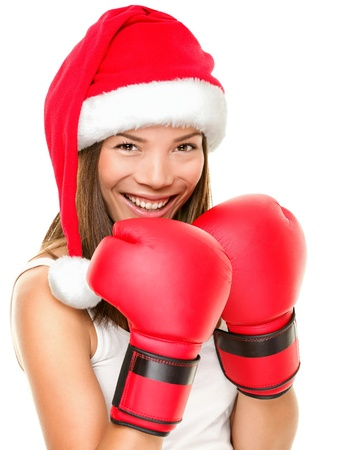 Christmas fitness boxing woman wearing santa hat and red boxing gloves. Funny portrait of happy smiling mixed race Asian Caucasian female fitness model isolated on white background.