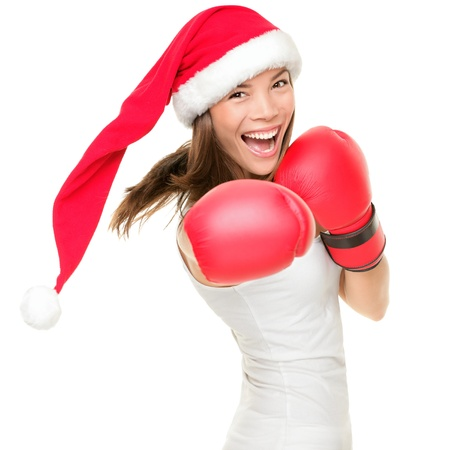 Christmas woman hitting wearing boxing gloves and red santa hat. Shopping boxing day or fitness concept. Beautiful fresh energy from asian caucasian female model isolated on white background.