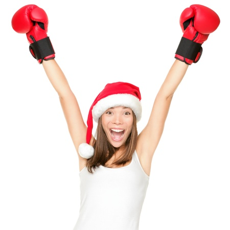 boxing training: Santa hat christmas woman celebrating wearing boxing gloves. Fitness or boxing shopping day concept. Winner energy from asian caucasian female model isolated on white background. Stock Photo