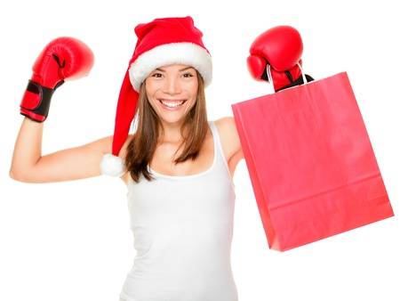 Christmas shopping boxing day concept with woman holding shopping bag wearing santa hat and boxing gloves. Funny fresh image of beautiful mixed race Asian Caucasian female model isolated on white background.