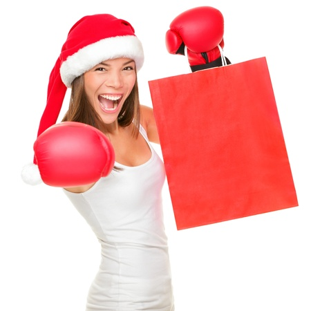 Boxing day shopping woman in Santa hat holding shopping bag with copy space. Energetic funny image of beautiful Caucasian / Asian female model isolated on white background. Archivio Fotografico