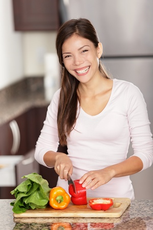Woman preparing food in kitchen making salad smiling happy. Beautiful mixed race Caucasian / Asian female model home in kitchen.