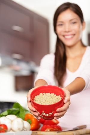 quinua: la quinua. Mujer mostrando plato de quinua que se utilizar� para cocinar ensalada saludable. Sonriente modelo femenino multirracial.