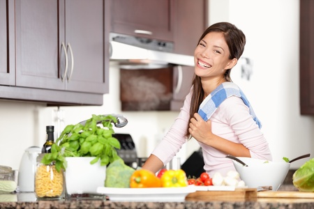 woman in kitchen making food smiling very happy and joyful. Lifestyle photo of mixed race Caucasian / Asian female model in her twenties in modern kitchen.